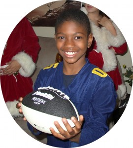 A happy child holding his new football.